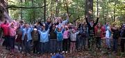 Viele Kinder und einige BetreuerInnen zwischen Bäumen im grünen Wald.