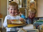 Kinder stöbern in Büchern aus den Bilderbuchtrögen