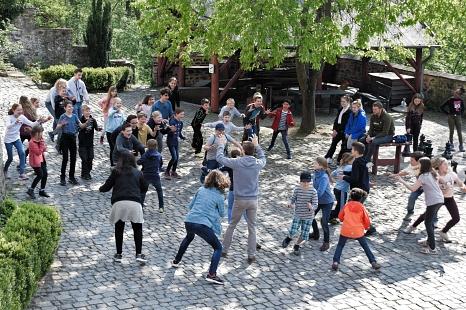Auf einem gepflasterten Hof stehen sich Kinder und Jugendliche gegenüber, bereit zum Fliehen oder Verfolgen.©Universitätsstadt Marburg