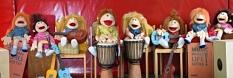 Zahlreiche Puppen sitzen nebeneinander und sind drapiert mit verschiedenen Musikinstrumenten.©Universitätsstadt Marburg
