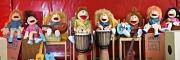 Zahlreiche Puppen sitzen nebeneinander und sind drapiert mit verschiedenen Musikinstrumenten.