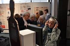 Die Erinnerungen von 13 Zeitzeugen gibt es an den verschiedenen Stationen per Bildschirm und Kopfhörer zu erleben. Wer sich setzen möchte, findet bequeme Sitzwürfel im Ausstellungsraum.©Stadt Marburg, Birgit Heimrich