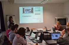 In einem Seminarraum sitzen links und rechts Teilnehmerinnen und Teilnehmer, eine Referentin steht neben einer Leinwand, auf der eine Präsentationsfolie (LibreOffice?) zu sehen ist.©Universitätsstadt Marburg