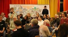 """Ein*e Teilnehmer*in aus jeder Gruppe trug ein Ziel und eine Maßnahme im Plenum vor. Diplom-Designer Christoph Illigens (im Hintergrund) hielt die Vorschläge in einem """"Graphic Recording"""" fest."""