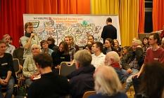 """Ein*e Teilnehmer*in aus jeder Gruppe trug ein Ziel und eine Maßnahme im Plenum vor. Diplom-Designer Christoph Illigens (im Hintergrund) hielt die Vorschläge in einem """"Graphic Recording"""" fest.©Birgit Heimrich, Stadt Marburg"""