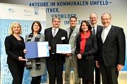 Das Marburger Team mit Gratulant/innen: Bürgermeister Wieland Stötzel (3. v. l.), Fachdienstleiterin Marion Kühn (2. v. l.) und Marburgs Klimaschutzmanager Achim Siehl (4. v. l.) nehmen den Klimaschutzpreis in Berlin entgegen.