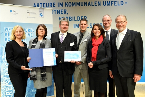 Das Marburger Team mit Gratulant/innen: Bürgermeister Wieland Stötzel (3. v. l.), Fachdienstleiterin Marion Kühn (2. v. l.) und Marburgs Klimaschutzmanager Achim Siehl (4. v. l.) nehmen den Klimaschutzpreis in Berlin entgegen.©(Foto: Peter Himsel/Difu)