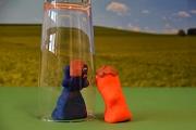 Ein blaue und eine rote Knetfigur mit einem Glas auf grünem Grund vor einem Fotohintergrund.