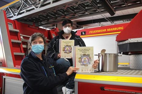 Carmen Werner (links), Leiterin der Feuerwehr, und Marita Schäfer, stellvertretende Stadtkinderfeuerwehrwartin, präsentieren das Koch- und Backbuch, das die Kinder der Marburger Kinderfeuerwehren zusammengestellt haben.©Viktoria Brüske, i. A. d. Stadt Marburg