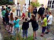 Zahlreiche junge Jugendliche und Betreuer spielen ein Kreisspiel, bei dem 2 Kissen möglichst schnell weiter gegeben werden müssen.