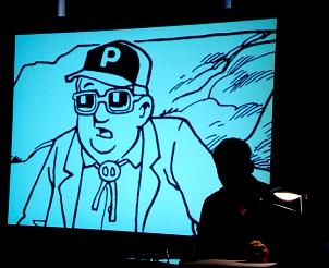 Live-Lesung mit einem Schauspieler im abgedunkelten Raum. Im Hintergrund auf einer Dia-Leinwand das große Bild eines Mannes mit Mütze.
