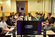 Im Vordergrund ein großer mit Monitor eingeblendeten Spielständen, links und rechts aufgereiht PCs auf Tischen mit zahlreichen Spielern.