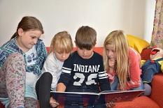 4 Kinder sitzen auf einem Sofa und schauen in ein Buch.©Universitätsstadt Marburg