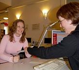 Eine lachende Mitarbeiterin der Stadtbücherei überreicht einer freundlichen Kundin an der Anmeldung Unterlagen.©Universitätsstadt Marburg