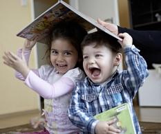 Zwei lachende Kleinkinder halten ein Bilderbuch über ihren Köpfen.©Stiftung_Lesen__Fotograf_Oliver_Ruether