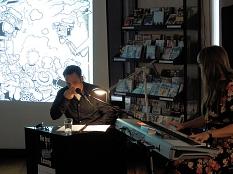 Ein Schauspieler liest aus einem Kinderkrimi, begleitet von einer Keyboarderin, im Hintergrund auf der Leinwand eine Bildszene aus dem Krimi.