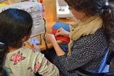 Eine Mitarbeiterin zeigt einem Mädchen Techniken mit Nadel, Faden und Nähmaschine.©Universitätsstadt Marburg