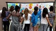 Zahlreiche Mädchen bemalen ein großes Tuch mit ihren Händen.