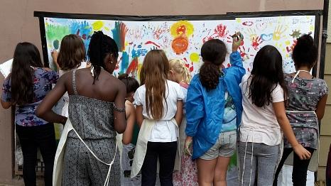 Zahlreiche Mädchen bemalen ein großes Tuch mit ihren Händen.©Universitätsstadt Marburg