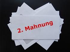 """Ein Stapel von Briefumschlägen, darunter auf einem Umschlag der rote Text """"2. Mahnung""""."""