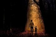 Ein Mann geht mit einem Kind an der Hand in den Wald.