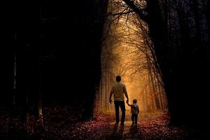 Ein Mann geht mit einem Kind an der Hand in den Wald.©pixabay