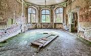 Innenansicht eines zerfallenden Raums mit drei großen Fenstern und einer auf dem Boden liegenden Tür.