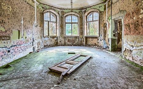 Innenansicht eines zerfallenden Raums mit drei großen Fenstern und einer auf dem Boden liegenden Tür.©Manuel Paulus