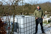 """Manuel Reuter von der """"GartenWerkStadt"""" vor den Wassertanks, die künftig an anderer Stelle Regenwasser für die Bewässerung der Beete speichern sollen - ein kleiner Beitrag für den Klimaschutz mit Vorbildfunktion."""