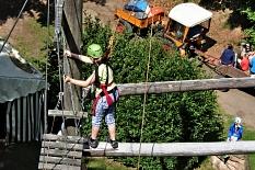 In ca. 8 Meter Höhe wartet eine Kletterin auf ihren Partner. Gemeinsam sollen beide 2 schwebende Balken queren. Unten im Hintergrund sieht man einen Trecker mit Anhänger.©Universitätsstadt Marburg