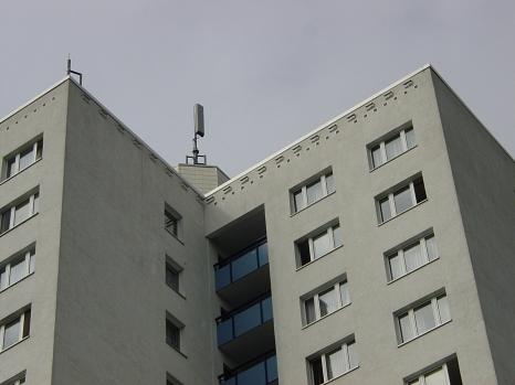 Teilansicht eines Hochhauses. Direkt unter der Gebäudeoberkante wurden zwanzig Nistkästen für Mauersegler angebracht, die nicht störend wirken, sondern eher die Fassadenansicht auflockern.
