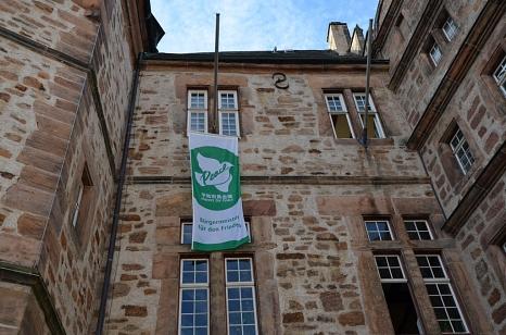 Oberbürgermeister Dr. Thomas Spies setzt vor dem Marburger Rathaus ein sichtbares Zeichen für eine friedliche Welt ohne Atomwaffen.©Tina Eppler, Stadt Marburg