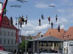 Einem Mobile gleich hängen Menschen an Kränen und spielen Musik©Scherbaum
