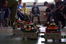 Mehrere Miniroboter fahren auf dem Boden, im Hintergrund die jugendlichen Programmierer.©Universitätsstadt Marburg