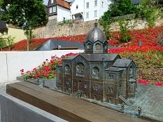 """Bronzemodell der zerstörten Synagoge vor dem """"Garten des Gedenkens"""" bei blühenden Rosen©Universitätsstadt Marburg"""