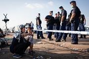 """Eine Frau mit einem kleinen Jungen vor einem Polizeiabsperrband – das Foto zeigt Menschen an den Außengrenzen Europas. """"Europa wählt Menschenwürde"""" heißt das diesjährige Motto der Internationalen Wochen gegen Rassismus."""