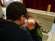 Ein Junge arbeitet an einer Nähnmaschine.