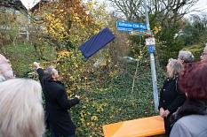 """Oberbürgermeister Dr. Thomas Spies enthüllt das neue Straßenschild des """"Katharina-Eitel-Wegs"""". Das Schild mit dem bisherigen Namen """"Walter-Voß-Weg"""" wurde zunächst symbolisch überklebt.©Stadt Marburg, Patricia Grähling"""