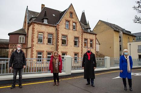 Oberbürgermeister Dr. Thomas Spies (2.v.r.) überreichte einen Zuwendungsbescheid in Höhe von 1,53 Millionen Euro für die Sanierung des Gebäudes am Krummbogen 2 (im Hintergrund zu sehen) an den JUKO-Vereinsvorsitzenden Dr. Thomas Wolf (v.l.), Marianne Wölk©Patricia Grähling, Stadt Marburg