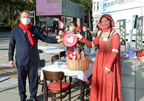 """Oberbürgermeister Dr. Thomas Spies (l.) übergibt für die Aktion """"Marburg isst solidarisch"""" einen Betrag von 200 Euro an Claudia Plociennik, als Heilige Elisabeth kostümiert.©Nadja Schwarzwäller i.A.d. Stadt Marburg"""