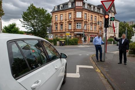 Oberbürgermeister Dr. Thomas Spies und Michael Hagenbring (Straßenverkehrsbehörde) zeigen den neuen Grünpfeil an einer Ampel am Wilhelmsplatz.©Patricia Grähling, Stadt Marburg