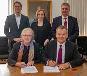 Oberbürgermeister Dr. Thomas Spies (vorne rechts) und Universitätspräsidentin Prof. Dr. Katharina Krause (vorne links) unterschreiben gemeinsam mit (v. r.) Bürgermeister Wieland Stötzel, Uni-Vizepräsidentin Prof. Dr. Evelyn Korn und Arne Kauffmann, stellv