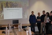 Schülerinnen und Schüler stehen rechts von einer Leinwand, auf der die Onlinebewerbungen vorgestellt werden.