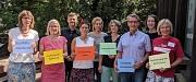 """Netzwerkteam der Marburger Patenschafts- und Mentoring-Projekte. Einige Personen halten farbige Karten mit Begriffen wie """"finanzielle Ressourcen"""", """"Austauschtreffen"""" oder """"Qualitätsstandards"""" hoch."""