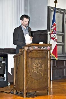 Prof. Dr. Ivo Züchner bei seinem Vortrag im historischen Saal des Rathauses. Er steht an einem Pult, neben ihm die Fahne Marburgs.©Universitätsstadt Marburg