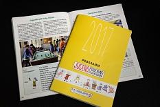Ein Foto des Programmheftes, einmal der gelbe Umschlag von außen, dahinter aufgeschlagen mit einer Doppelseite Text und Bildern©Universitätsstadt Marburg