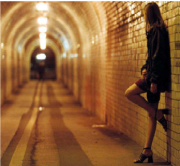 Eine Prostituierte steht an der Straße.