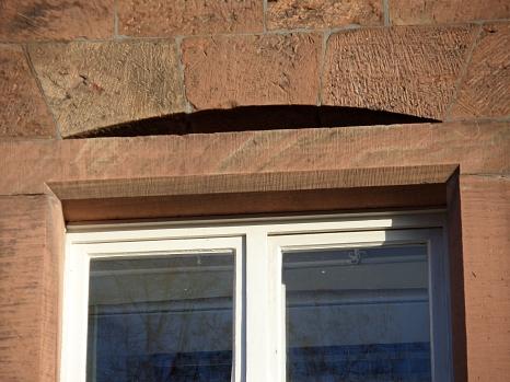 Nahaufnahme einer Sandsteinfassade. Über dem Fenster befindet sich eine Höhlung, die als Fledermausquartier geeignet ist.