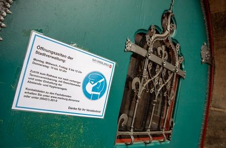 Ein Aushang an der Rathaustür weist auf die Öffnungszeiten und die Regeln beim Betreten der Gebäude hin.©Patricia Grähling, Stadt Marburg