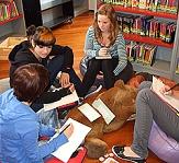 Vier Schülerinnen sitzen im Kreis auf Sitzkissen, vor sich Papier und Stifte, um an einem Thema zu arbeiten.©Universitätsstadt Marburg